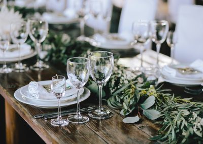 Decorated elegant wooden wedding table in rustic style with eucalyptus and flowers, porcelain plates, glasses, napkins and cutlery